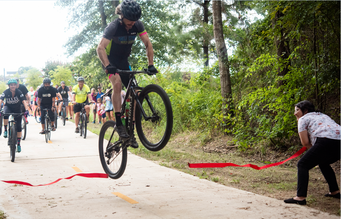 Bike jumping over ribbon at the Grand Opening of Legacy Trail