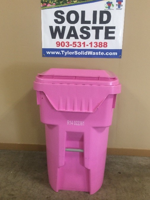 A large pink garbage container